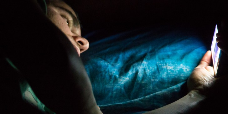 Man laying on bed at late night in a dark room checking his smartphone. Internet addiction.